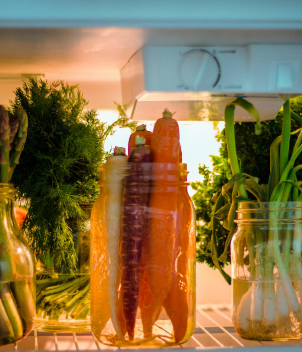 Image of Asparagus and carrots in in a mason jars lined up next to each other in a refrigerator.