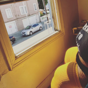 Image of Brena Jean in a yellow pair of plus size thigh high socks facing an open window to a urban street.