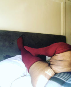 Image of Brena Jean's legs posed on headboard wearing red plus size thigh highs