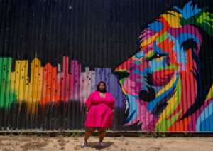 Image of plus size black woman with lipedema in her arms and legs wearing a short pink dress exposing the texture of her thighs. She is standing in from of a colorful mural showing the side profile of a lion. The lions profile is painted in red, blue, yellow, black, green, and purple. Extended from the front of the lions face are a row of city buildings of different colors. The city buildings are green, yellow, red, purple, and and pink.