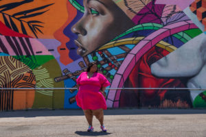 """Image of Brena, a fat black woman with lipedema wearing Rebdolls """"Cut it Out"""" skater dress which is v-neck, pink, and above the knee. Wearing Puma Future Rider Play on Casual Shoes. She is standing in front of a mural of a black woman's side profile in a myriad of plants, geometric shapes, and a rose."""