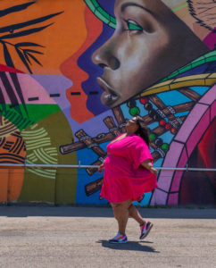 Image of Brena, a fat black woman with lipedema walking towards the left side of the photo while playing with her pink knee-length dress and looking up towards the sky smiling. Behind her is a mural that prominently shows the side profile of a black woman in a myriad of geometric patterns and plants.
