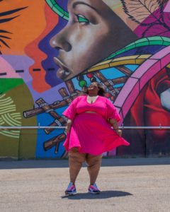 Image of Brena, a fat black woman with lipedema laughing with her hear back looking at the sky. She's wearing a knee-length pink dress with a cut-out on the stomach. She's standing in front of a mural depicting the side-profile of a black woman.