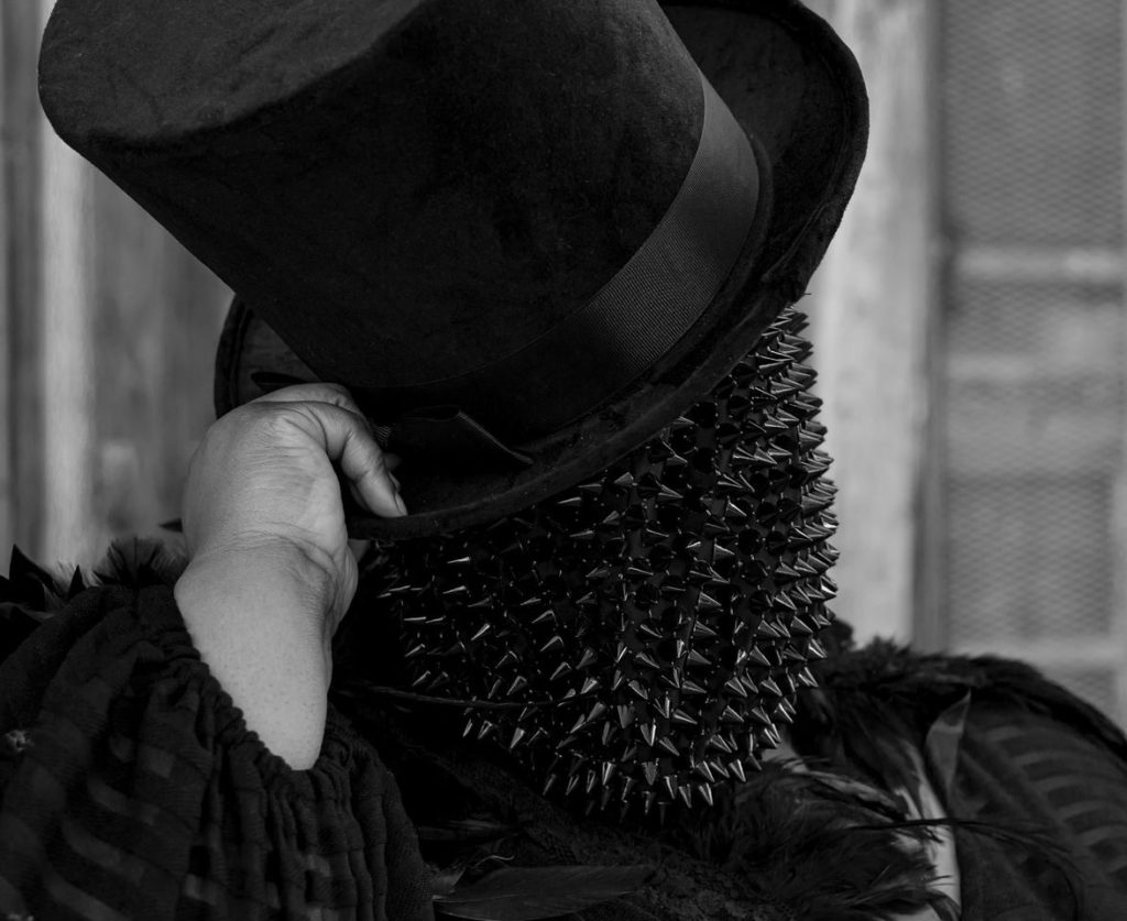 This is a close up black and white image of me, a fat black woman, wearing a spiked full-face mask and black tophat and sheer, black Jibri gown. I am tipping my top hat and looking at the camera.