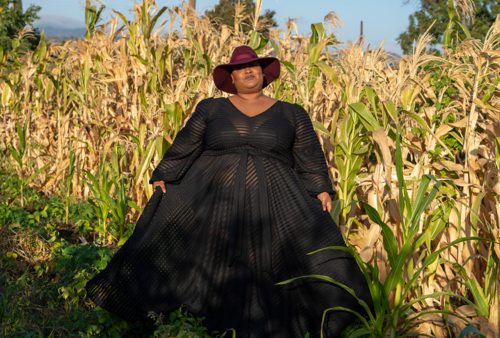 Image of me, a fat black woman standing in a corn field. I'm wearing a burgandy fedora and sheer black gown by Jibri. This is a full length photo and I'm holding the bottom of my dress out at the sides.