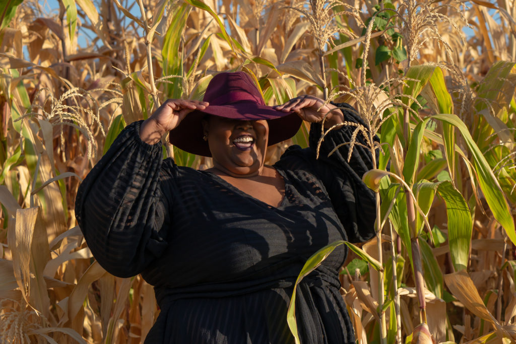 An image of me, wearing a sheer, black, Jibri dress and burgandy fedora. I'm standing in a corn field with both hands holding the brim of the fedora over my eyes.