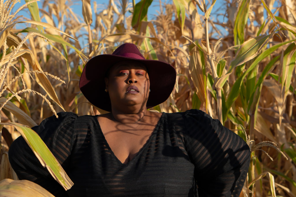 Image of me, a fat black woman standing in a corn field. I'm wearing a burgandy fedora and sheer black gown by Jibri. I'm in a confident stance with my hands on my hips and facing forward.