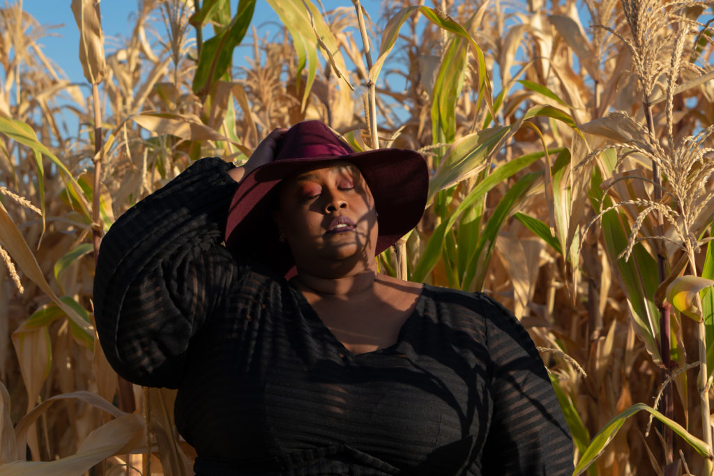 Image of me, a fat black woman standing in a corn field. I'm wearing a burgandy fedora and sheer black gown by Jibri. I'm holding the back of my fedora and my eyes are closed and my face is tilted upward towards the sun. There are shadows from the surrounding cornfield on my face.
