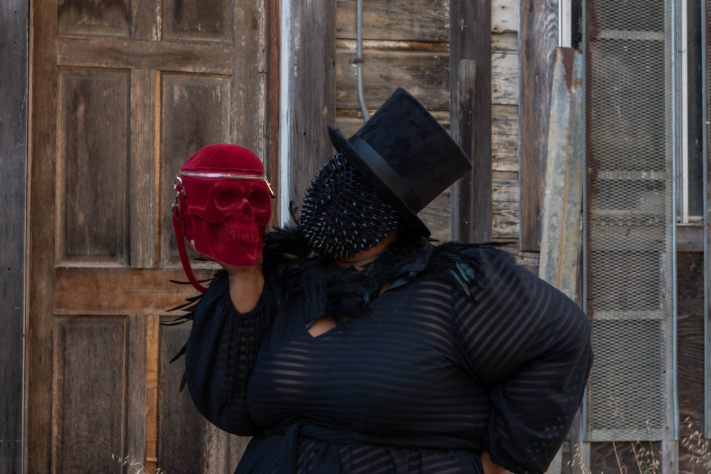 Image of me, a fat black woman standing in front of an old rickety brown door. The background looks spooky. I'm wearing a black top hat with the sheer black gown by Jibri. I have on a spiked black mask that covers my whole face under the tophat. I'm holding red velvet skull purse is resting atop my palm, next to my face and my face is turned away from the camera and facing the purse.