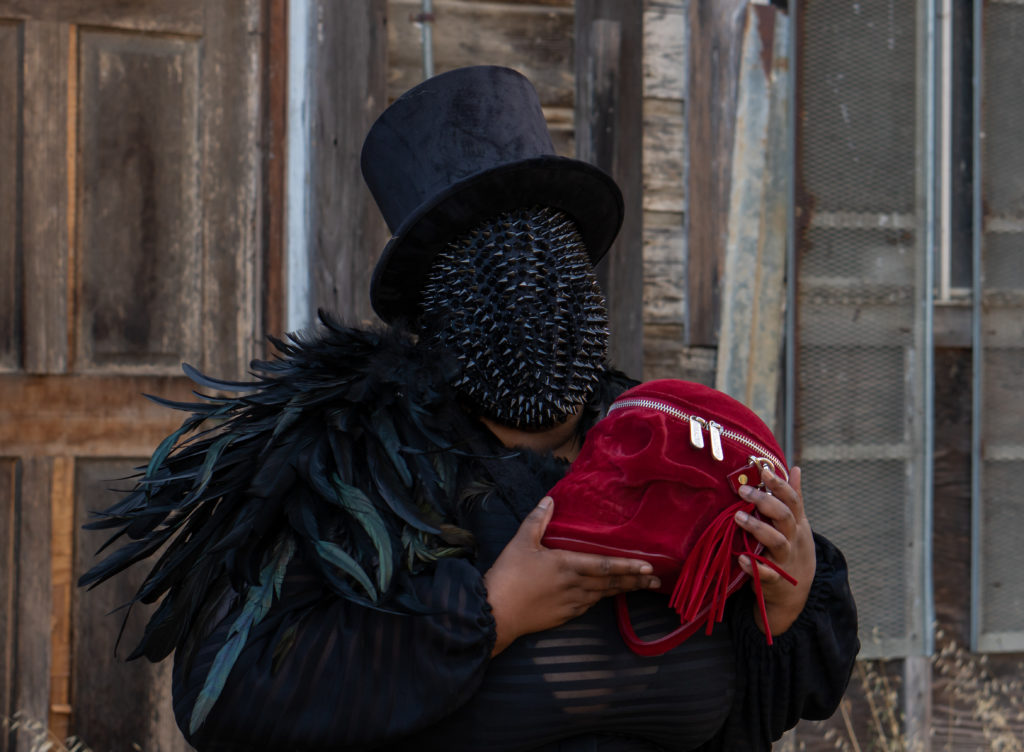 Image of me, a fat black woman standing in front of a old abandoned home with a brown door. I'm wearing a black top hat and the sheer black gown by Jibri. I'm holding a red velvet skull purse, with both hands to my chest. My face is covered by a black spiked mask and I'm wearing black and dark green feathers on my right shoulder.