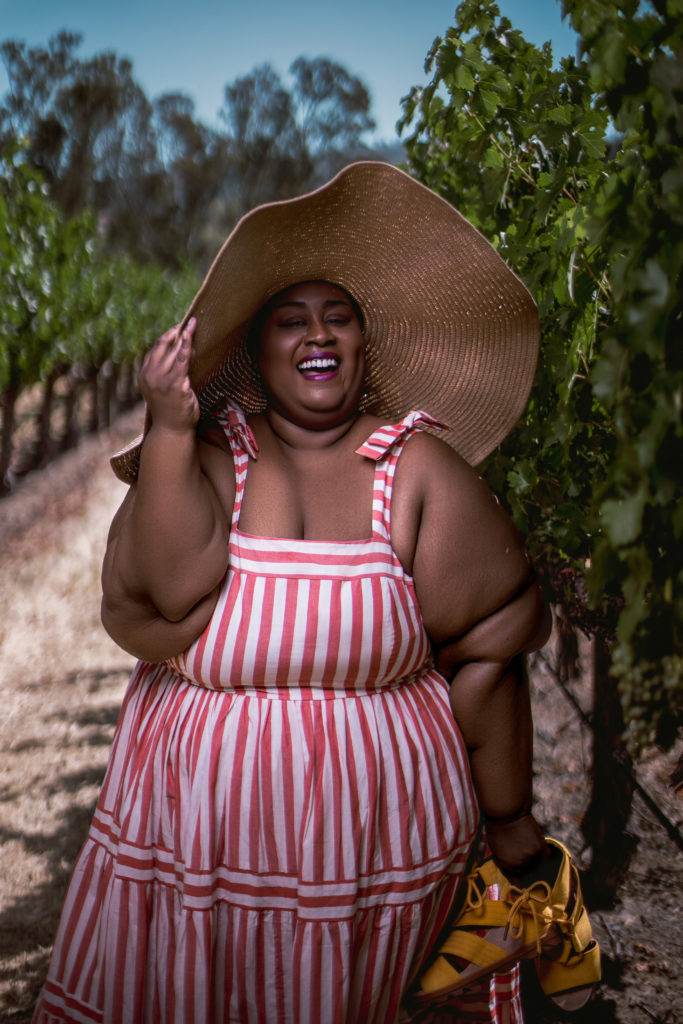 Image of Brena Jean in a grape vinyard. She is a fat, brown skin Black woman, wearing a tan-colored sun hat and a plus size striped coral dress with bows on the shoulder and holding a pair of yellow wedge sandals. She is smiling and her eyes are closed.